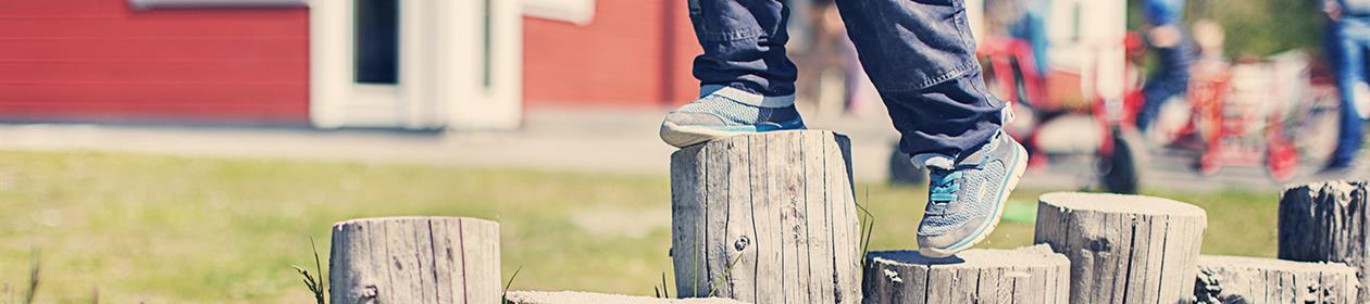Barneføtter som balanserer på stubber