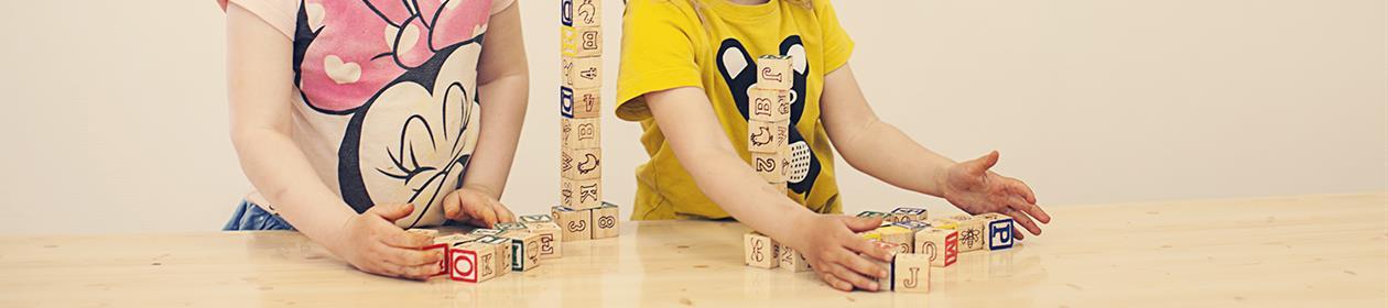 Barnehender stabler klosser med bokstaver på.