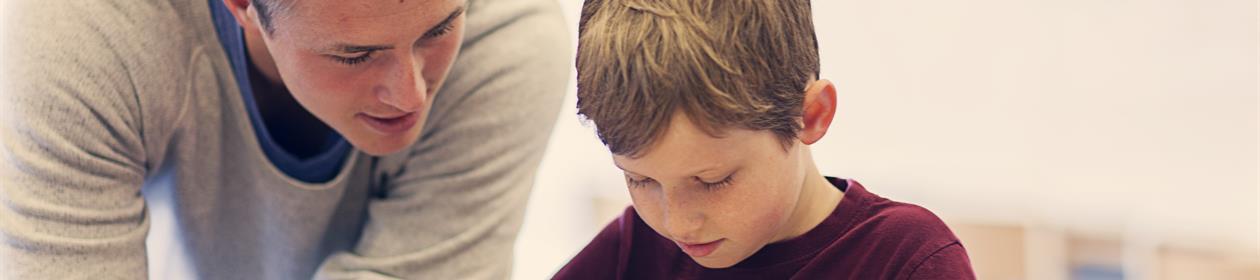 mannlig, ung lærer hjelper gutt med å lese