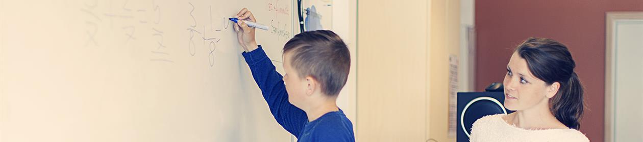 Kvinnelig elev ser på gutt som skriver på tavla.