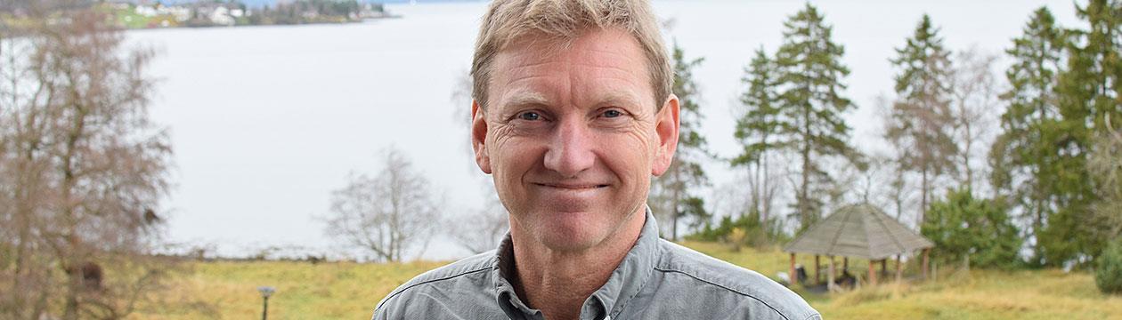 Ivar Svare Holand utenfor kontoret i Levanger, med havutsikt i bakgrunnen