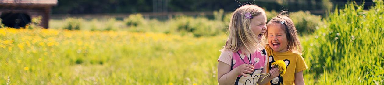 To jenter ler og leker i gresset