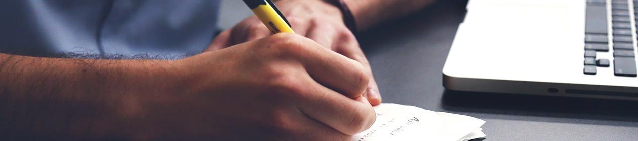 Mann skriver på blokk